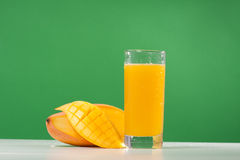 Mango juice. Fresh mango juice in a glass over green background Royalty Free Stock Photography