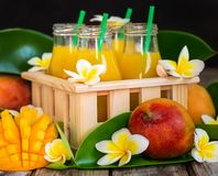 Mango juice. Fresh mango juice in small bottles in wooden box Stock Photography