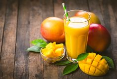 Mango juice in the glass. With straw on the wooden table Royalty Free Stock Photos