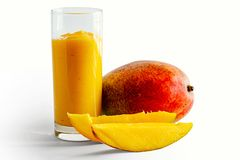 Mango juice in a glass and pieces of mango Royalty Free Stock Photography