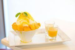 Mango kakigori Japanese shaved ice dessert flavor with mango. Ice-cream serve on white bowl with yellow mango sauce & white milk for sweet food background or Stock Images