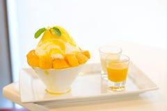 Mango kakigori Japanese shaved ice dessert flavor with mango. Ice-cream serve on white bowl with yellow mango sauce & white milk for sweet food background or stock images