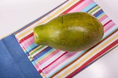 Mango. On kitchen cloth with stripes Stock Photos