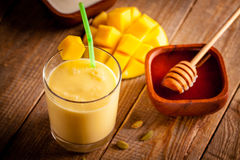 Mango lassi. Glass of mango lassi, Indian drink made from yogurt with blended mango and honey, flavored with cardamom Stock Image