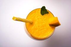 Mango Lassi o frullato in grande vetro con la foglia della menta Angolo laterale isolato sopra fondo colourful immagini stock