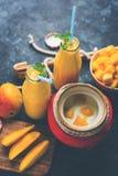 Mango Lassi o frullato in grande vetro o piccole bottiglie con cagliata, i pezzi tagliati della frutta ed il miscelatore fotografia stock libera da diritti