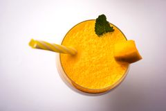 Mango Lassi or smoothie in big glass with mint leaf. Side angle  Isolated over colourful background Stock Images