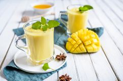 Mango Lassi - traditional Indian yoghurt drink. In a glass jars stock photography