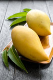 Mango and leaves in wood tray on wood table Royalty Free Stock Photography