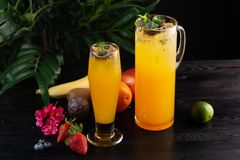 Mango lemonade - passion fruit in a jug and a glass and fruit on a wooden background royalty free stock image