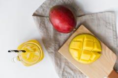 Mango maduro, medio mango y un vidrio de jugo del mango con un tubo en una tabla de cortar de madera imagen de archivo libre de regalías