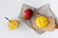 Mango maduro, medio mango y un vidrio de jugo del mango en una tajadera de madera fotos de archivo