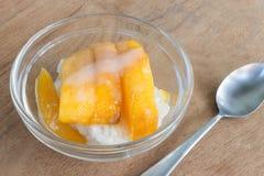 Mango med ris klibbar, och kokosnöten mjölkar på wood bakgrund Fotografering för Bildbyråer