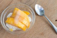 Mango med ris klibbar, och kokosnöten mjölkar på wood bakgrund Royaltyfri Bild