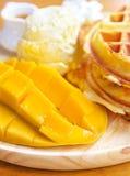 Mango met wafel en roomijs op houten raad stock foto