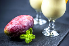 Mango and mint with mango lassi. Mango and mint with two glasses of mango lassi on black background Stock Photography