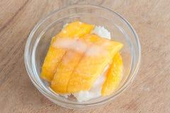 Mango mit Reisstock und -Kokosmilch auf hölzernem Hintergrund Stockfoto