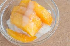 Mango mit Reisstock und -Kokosmilch auf hölzernem Hintergrund Lizenzfreies Stockfoto