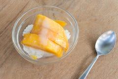 Mango mit Reisstock und -Kokosmilch auf hölzernem Hintergrund Stockbild