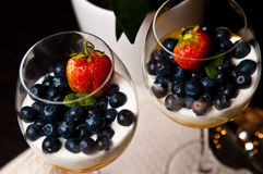 Mango mousse with blueberries in wine glasses Stock Photos