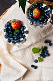 Mango mousse with blueberries in wine glasses stock photo