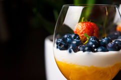 Mango mousse with blueberries in wine glasses royalty free stock images