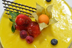 Mango mousse cake. Decorated with strawberries, raspberries and blueberries Stock Photos