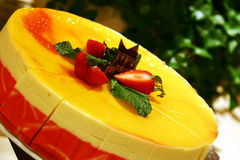 Mango Mousse Cake. Delicious Mango Mousse Cake topped with strawberries and chocolate royalty free stock images
