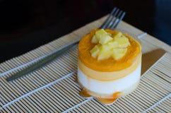 Mango mousse cake on wooden background Stock Photos