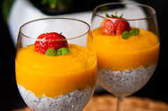 Mango mousse with chia seeds and coconut milk. An elegant table setting with homemade mango mousse with chia seeds, coconut milk, natural yoghurt, maple syrup royalty free stock photo