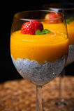 Mango mousse with chia seeds and coconut milk. An elegant table setting with homemade mango mousse with chia seeds, coconut milk, natural yoghurt, maple syrup Royalty Free Stock Image