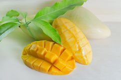 Mango nicely cut with leaf. Mango ripe with nicely cut pieces and leaf on wooden board (Other names of mango are horse mango, Mangifera foetida, Anacardiaceae Stock Photo