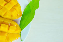 Mango nicely cut with leaf on wooden background (Also known as h. Mango ripe with nicely cut pieces and leaf on wooden board (Other names are horse mango Stock Photo