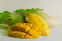 Mango nicely cut with leaf on wooden background (Also known as h. Mango ripe with nicely cut pieces and leaf on wooden board (Other names are horse mango Stock Images