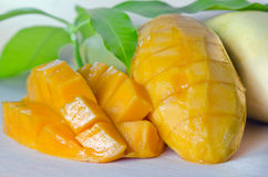Mango nicely cut with leaf on wooden background (Other names of. Mango ripe with nicely cut pieces and leaf on wooden background (Other names of mango are horse Royalty Free Stock Photo