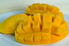 Mango nicely cut on the plate on wooden background (Also known a. Mango ripe with nicely cut pieceson the plate on wooden board (Other names are horse mango Royalty Free Stock Photos