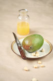 Mango op een plaat met macadamia noten Stock Fotografie