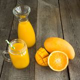 Mango and orange juice and slice of orange on wooden table. Fresh healthy tropical drink. Close up. Stock Image