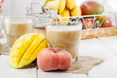 Mango and peach smoothie on wooden table with ingredients. Stock Photography