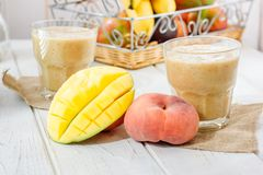 Mango and peach smoothie on wooden table with ingredients. Stock Image