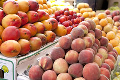 Mango and peaches fruit at the outdoor market. Royalty Free Stock Photography