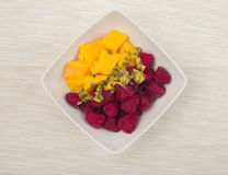 Mango pieces and raspberries with passion fruit in a white bowl on beige fabric background Royalty Free Stock Photo