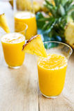 Mango with pineapple smoothie. In jug and glasses Stock Photos