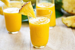 Mango with pineapple smoothie. In jug and glasses Stock Image