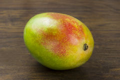 Mango ripe fresh red green yellow natural vitamins tropical life on wood Stock Photography