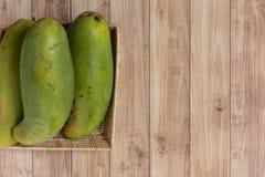 Mango's in mand op houten achtergrond Stock Afbeelding