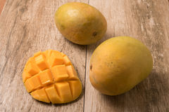 Mango slice cut to cubes with fresh mango on wooden table Royalty Free Stock Photo
