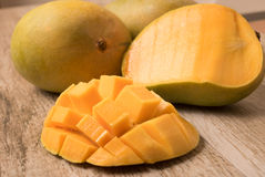 Mango slice cut to cubes with fresh mango  on wooden table. Stock Photos
