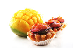 Mango and small fruit cakes. Uncooked mango and small fruit cakes served Stock Photo