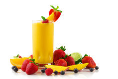 Mango smoothie. A glass of mango smoothie surrounded by fresh fruits